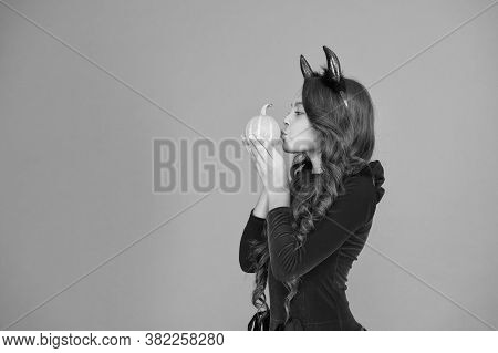 Kiss Spell. Small Girl Kiss Pumpkin Orange Background. Little Child Wear Red Devil Horns For Holiday