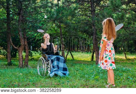 A Young Disabled Girl Plays Badminton With Her Younger Sister. Interaction Of A Healthy Person With