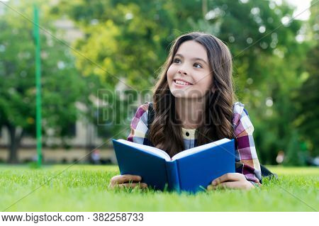Let Your Creative Ability Investigate. Happy Child Read Book Lying On Green Grass. Reading Education