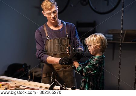 Brothers Prepare A Gift Made Of Wood For Their Mother In The Garage