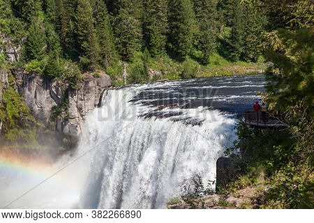 A Rainbow In The Mist Of Upper Mesa Falls As It Cascades Over A Cliff In The Rugged Wilderness Of He