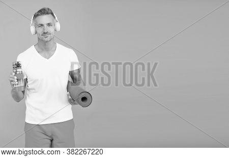 Choose Sport Drink Wisely. Athletic Man Hold Sport Bottle And Gym Mat. Handsome Sportsman Blue Backg