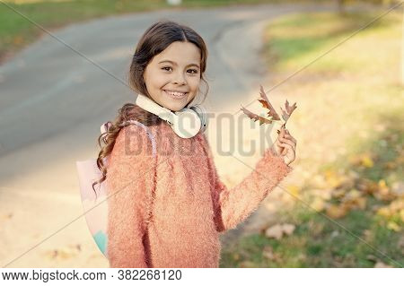 Kid Girl Relaxing Autumn Leaf With Modern Wireless Headphones. Music For Autumn Cozy Mood. Listening