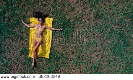 beautiful woman in bikini lying on a meadow