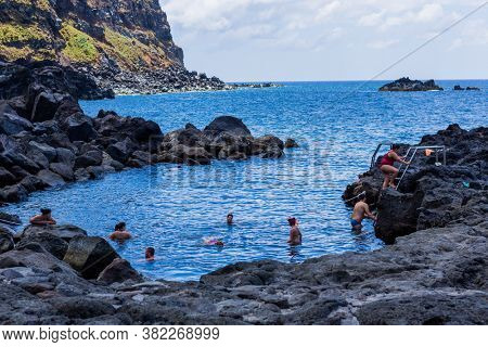 Ponta da Ferraria, Azores, Portugal - August 13, 2020: People bathing in natural volcanic thermal pool in Ponta da Ferraria, the place where hot springs mix with seawater.