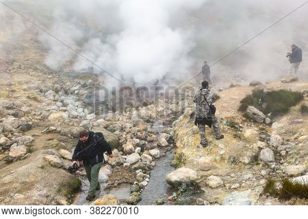 Group Of Travelers And Photographer Walks Through Volcanic Landscape: Hot Springs, Eruption Fumarole