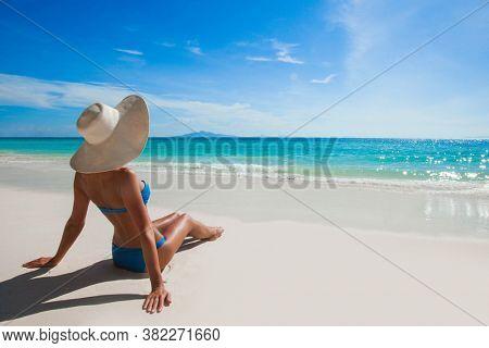 Beautiful tan woman in bikini lies on white sand beach looking on the sea, back view