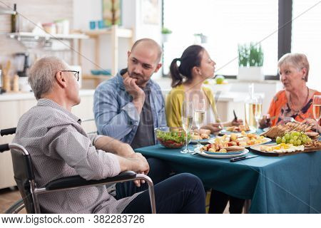 Disabled Senior In Wheelchair Man Having A Conversation With Son During Family Brunch In Kitchen. Se