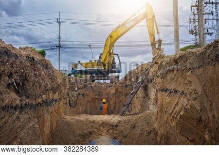 Backhoe Excavator Digging A Trench For Installation Water Pipeline Underground At Construction Site.