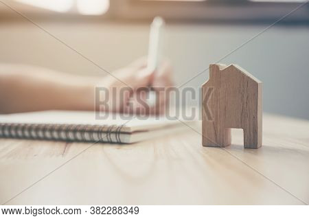 Close Up Hand Of Man Take Notes In A Notebook Plan To Be A Landlord With Wooden House Model. Mortgag