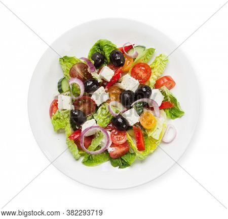 Greek salad with cucumber, tomato, pepper, lettuce, onion, feta cheese and olives, dressed with olive oil. Top view flat lay isolated on white