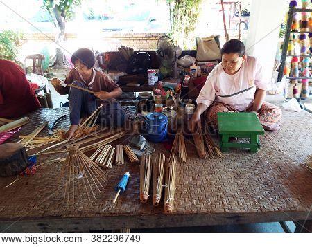 Bor Sang, Chiang Mai, Thailand, December 22, 2018: Two Artisans Cut Bamboo To Make Umbrellas At The