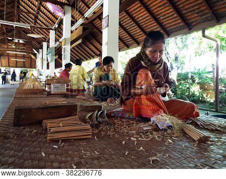 Bor Sang, Chiang Mai, Thailand, December 22, 2018: Craftswomen Cut Bamboo To Make Umbrellas At Bor S