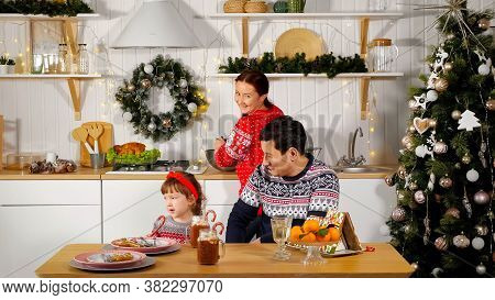 Mother Cooks Festive Supper And Smiling Father Sits With Cute Girl Kid At Table In Kitchen Near Deco