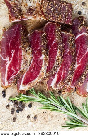 Useful Meat Products Made At The Meat Production Plant, Close-up Of Sliced Meat With Green Fresh Ros
