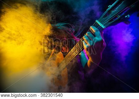 Playing Guitar. Young Woman With Smoke And Neon Light On Black Background. Highly Tensioned, Wide An