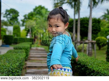 A Cute Young Asian Girl With A Bright Blue Shirt Is Strolling Around In A Park With Stone Walkway, T
