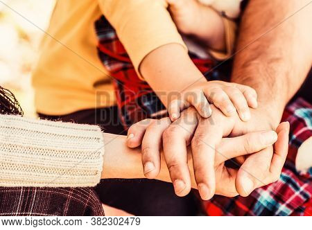 Concept Of Unity, Support, Protection, Happiness. Parents Hold The Baby Hands. Closeup Of Baby Hand