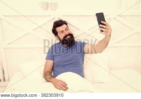 Taking Selfie. Cellular Communication. Modern Guy Talking On Smartphone In Bed. Handsome Man With Mo