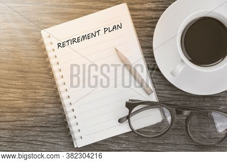 Retirement Plan Word On Notebook With Glasses, Pencil And Coffee Cup On Wooden Table. Retirement Pla