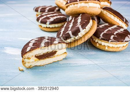 Cookies With White Filling And Chocolate Glaze On The Table