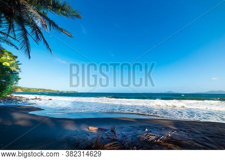 Dark Sand In Grande Anse Beach In Guadeloupe, French West Indies. Lesser Antilles, Caribbean Sea