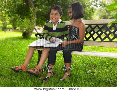 Asian Kids Of Indian Origin Reading A Book In A Park