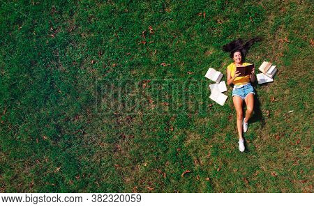 woman lying on a meadow reads a book