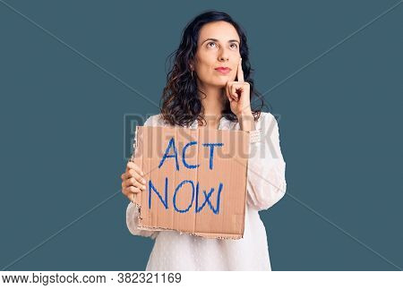 Young beautiful hispanic woman holding act now banner serious face thinking about question with hand on chin, thoughtful about confusing idea