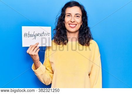 Young beautiful hispanic woman holding paper with hashtag body positive looking positive and happy standing and smiling with a confident smile showing teeth