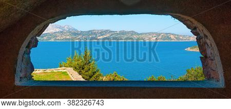 Capo Coda Cavallo Shore Seen Through A Rustic Arch. Sardinia, Italy