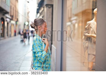 beautiful woman looks at the window of a clothes shop