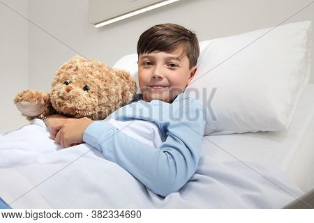 Portrait Of Cute Happy Child Alone In Hospital Room Lying In Bed With Teddy Bear Looking At Camera A