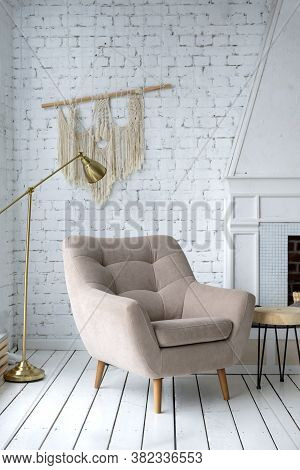 1 Beige Armchair In A Bright Room Against A White Wall, Fireplace