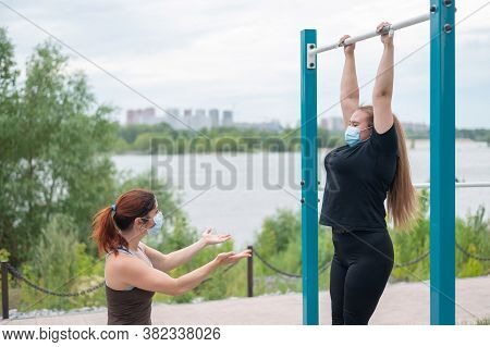 A Female Personal Trainer Helps A Fat Client To Pull Herself Up On Horizontal Bars Correctly. Two Wo