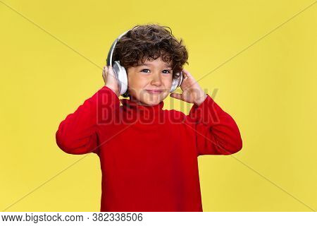 Listening To Music. Portrait Of Pretty Young Curly Boy In Red Wear On Yellow Studio Background. Chil