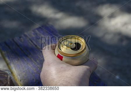 Male Hand With An Aluminum Can Of Beer. Opened Can Of Lager Beer. Quenching Thirst On A Hot Summer D