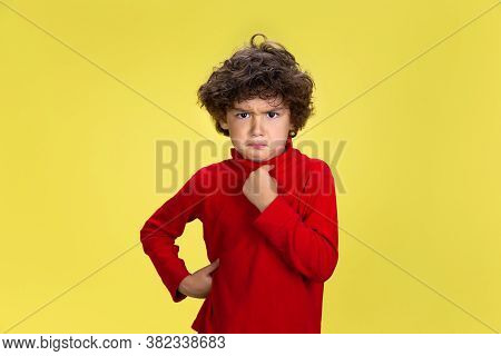 Pointing At Himself. Portrait Of Pretty Young Curly Boy In Red Wear On Yellow Studio Background. Chi