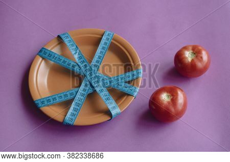 Fresh Tomatoes On Purple Background And Plate Tied With Measuring Tape. Two Ripe Tomatoes And Clay P