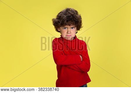Offended. Portrait Of Pretty Young Curly Boy In Red Wear On Yellow Studio Background. Childhood, Exp