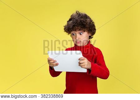 Using Tablet. Portrait Of Pretty Young Curly Boy In Red Wear On Yellow Studio Background. Childhood,