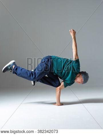 Cool Guy Breakdancer Dancing Breakdance On The Floor In Studio Isolated On Gray Background. Break Da