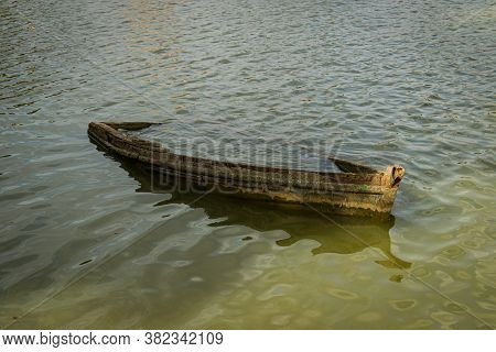 Old Wrecked Boat Half Submerged At The Shore Of Lake