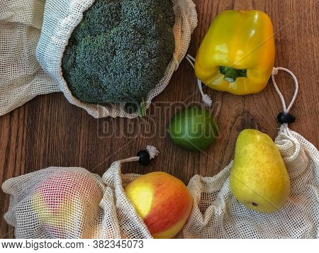 Fresh Fruit And Vegetables Close Up In Cotton Bags Top View. Broccoli, Pepper, Lime, Par, Apples. Ec