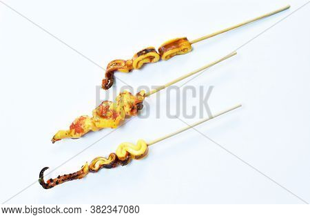 Grilled Squid Dressing Spicy Sauce Stabbing In Wooden Stick On White Background