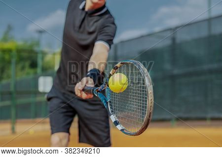 Close Up Of Man Playing Tennis At Court And Beating The Ball With A Racket. Player Is Hitting Ball W
