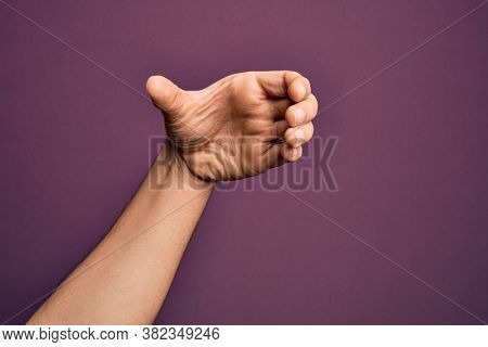 Hand of caucasian young man showing fingers over isolated purple background holding invisible object, empty hand doing clipping and grabbing gesture