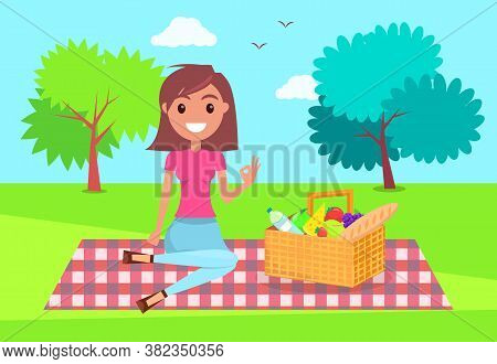 Young Girl Sitting At Checkered Plaid In Park With Basket Full Of Products. Smiling Girl Relaxing At
