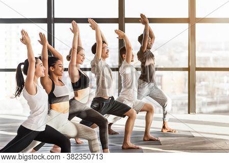 Multicultural Yoga Class Members Standing In Warrior One Pose, Practicing Virabhadrasana I Asana, Tr