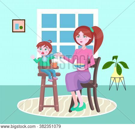 Mother Feeding Her Little Son With A Poridge Or Other Meal Sitting In Children S Chair. Boy Denying